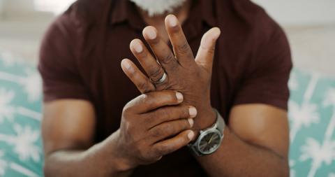 Person with arthritis rubbing a sore hand.