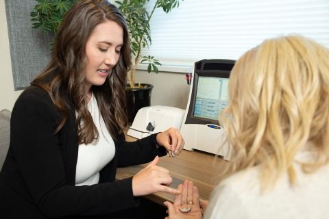 An Audiologist helps a customer choose hearing aids at Broadmead Hearing